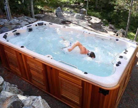Man swimming in an Arctic Spas All Weather Pool