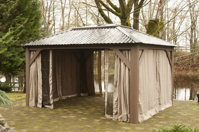 The side view of an open air Arctic Spas Gazebo with an open insect screen , model Della