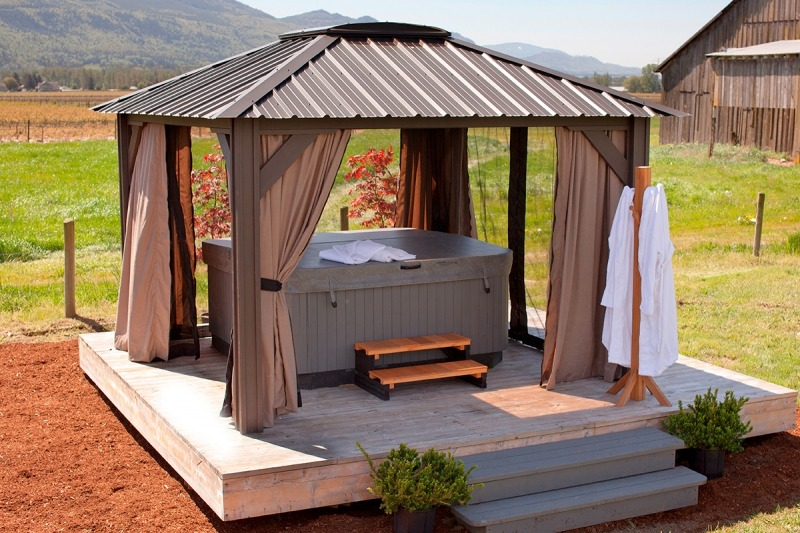 The side view of an open air Arctic Spas Gazebo Milano, with a hot tub inside