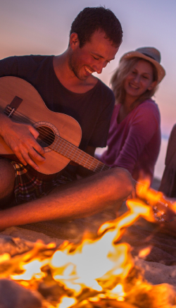 Man playing guitar by the fire