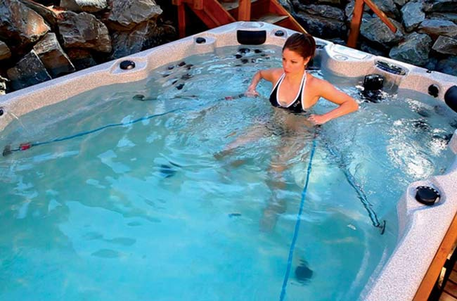 A woman rowing in the swim spa.